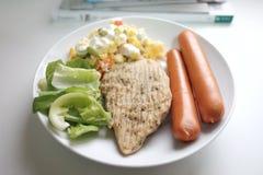En foco selectivo un plato blanco del filete del pollo de la pimienta con la ensalada de las verduras frescas y de atún de la zan fotografía de archivo libre de regalías