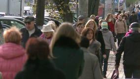 En folkmassa av folk går runt om stad lager videofilmer