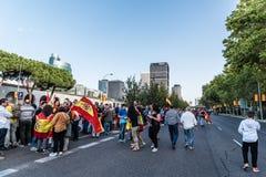 En folkmassa av folk med flaggor i spansk nationell dag ståtar Arkivfoton