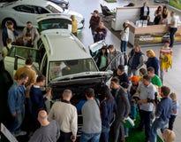 En folkmassa av folk nära den nya bilen i visningslokalen Royaltyfri Fotografi