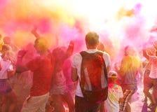 En folkmassa av folk som firar den Holi festivalen arkivbilder