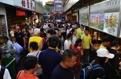 En folkmassa av folk som går till och med Pekinggatorna arkivfoto