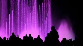 En folkmassa av turister som håller ögonen på en show av magiska dansa springbrunnar arkivfilmer