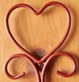 En forma de corazón del alambre de metal marrón con el fondo de madera Imagen de archivo