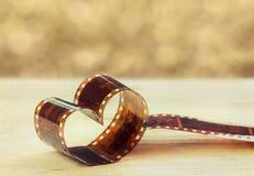 En forma de corazón hecha de negativa de película retra en el tablero de madera contra fondo del bokeh Imagenes de archivo