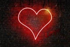 En forme de coeur au néon rouges se connectent un mur de briques humide Image libre de droits