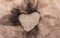 En forme de coeur brûlé hors d'un papier Photos libres de droits