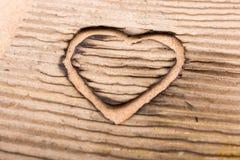 En forme de coeur brûlé hors d'un carton Image stock
