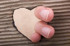 En forme de coeur brûlé hors d'un carton Photo stock