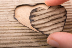 En forme de coeur brûlé hors d'un carton Photos libres de droits