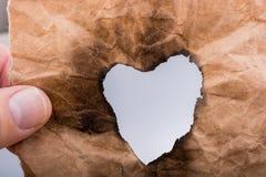 En forme de coeur brûlé hors d'un papier Photographie stock libre de droits