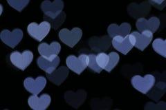En forme de coeur coloré sur le bokeh noir d'éclairage de fond pour la décoration au papier peint de contexte de nuit a brouillé  Photo libre de droits