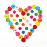 En forme de coeur des boutons de couture colorés sur le blanc Images stock