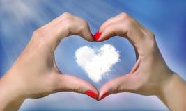 En forme de coeur des mains contre le ciel bleu clair Images libres de droits