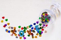 En forme de coeur lumineux de confettis dispersé d'un verre à vin Photographie stock libre de droits