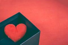 En forme de coeur rouge dans un boîte-cadeau noir pendant un jour du ` s de Valentine Photo libre de droits