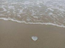 En forme de coeur sur la plage de sable images libres de droits