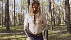 En formidabel krigare står i mitt av skogen och ser hans vapen och ser därefter omkring Kameran ?r i r?relse arkivfilmer