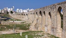 En forntida akvedukt sträcker över en modern stad Royaltyfri Fotografi