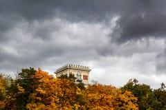 En forntida byggnad bland lövverket och den annalkande thunden Arkivfoto
