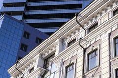 En forntida byggnad bredvid en modern kontorsbyggnad abstrakt bild av moderna och historiska former av byggnader Royaltyfria Bilder