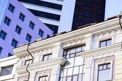 En forntida byggnad bredvid en modern kontorsbyggnad abstrakt bild av moderna och historiska former av byggnader Fotografering för Bildbyråer