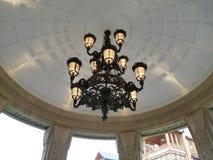 En forntida ljuskrona med ljusa kulor som hänger i en dagdrivare på gatan royaltyfri foto