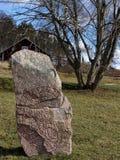 En forntida skandinavisk runsten Röd runatext och drwaing Arkivfoton