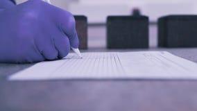 En forskare gör anmärkningar på papper lager videofilmer