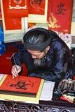 En forskare skriver kinesiska kalligrafitecken på templet av litteratur Royaltyfri Bild