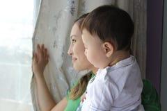 Fostra och sonen som ser i fönster Royaltyfria Bilder