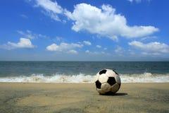 En fotboll på en strand Arkivfoto