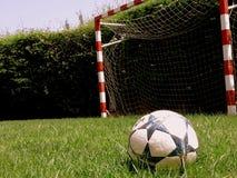 En fotbollboll i förgrunden på ett grönt gräs och ett mål i bakgrunden Royaltyfri Bild
