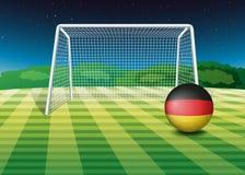 En fotbollboll nära det netto med flaggan av Tyskland Royaltyfria Bilder