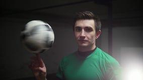En fotbollman som rotera fotbollbollen på hans finger och ser i kameran lager videofilmer