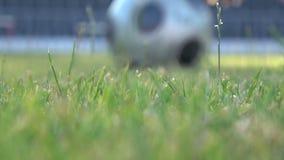 En fotbollspelare slår bollen under en match på fotbollfältet arkivfilmer
