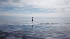 En fotbollsspelare står i mitt av Lake Baikal Pittoreska Lake Baikal knäcker blåa glansiga klara ismindre kulle arkivfilmer