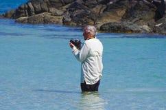 En fotograf som upp till står hans avfalls i havet Royaltyfria Bilder