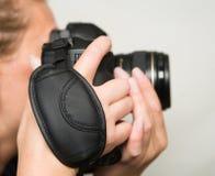 En fotokamera med ett handledbälte i härliga kvinnliga händer royaltyfri fotografi