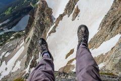 En fotvandrare dinglar hans ben över kanten av en klippa i Rocky Mountains Arkivfoton