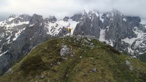 En fotvandrare står överst av ett berg och blickar på snö-korkade berg och att lyfta hans händer i segergest stock video