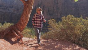 En fotvandrarekvinna går på Trekking vandringsled som det rött vaggar av Zion Canyon lager videofilmer