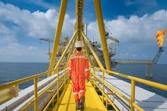 En frånlands- oljeplattformarbetare går till den centrala lättheten för fossila bränslen till att arbeta i processområde, underhå royaltyfri fotografi