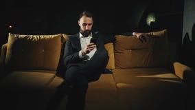 En framgång och en lycklig skäggig affärsman använder sent hemmastatt för mobiltelefon, frilans- längd i fot räknat 4k arkivfilmer