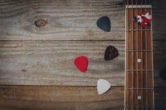 En fretboard för akustisk gitarr och några gitarrhackor på trätabellen arkivbild