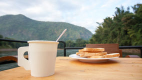 En frukost, kaffe i pappers- kopp med bröd med natursikt Royaltyfria Foton