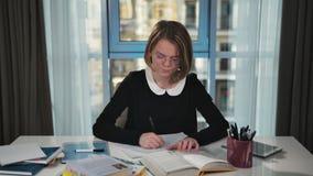 En frustrerad skolflicka som gör läxa Läser en bok och skriver i en skrivbok, efter den har korsat ut och har fått ilsken stock video