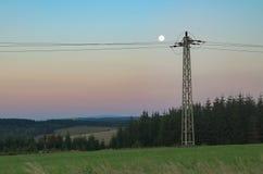 En fullmåne ovanför kraftledningen Arkivbild