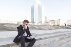 En fundersam affärsman som sitter på en trappuppgång med en bärbar dator på hans knä mot en bakgrund av det stads- landskapet arkivbild