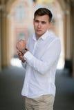 En fundersam affärsman som trycker på hans svarta klocka En nätt grabb som går utanför på en stads- bakgrund bakgrundsbegrepp som royaltyfri foto